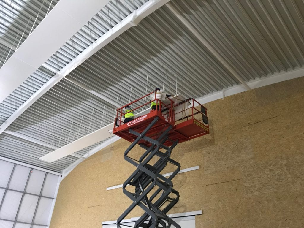 Solray installers fitting free hanging radiant panels at Badminton School